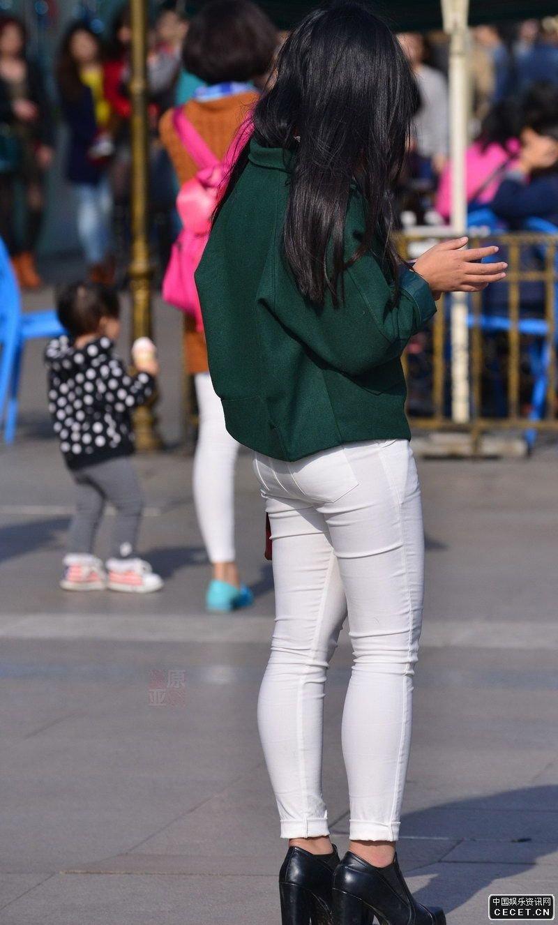 公园门口街拍的紧身白裤美女图片